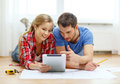 Smiling couple looking at tablet pc at home repair building renovation and concept Royalty Free Stock Images