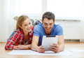 Smiling couple looking at tablet pc at home repair building renovation and concept Stock Photo