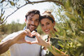 Smiling couple making heart shape by trees at olive farm Royalty Free Stock Photo