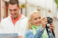 Smiling couple with map and photocamera in city travel vacation technology friendship concept exploring Royalty Free Stock Photo