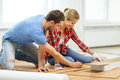 Smiling couple measuring wood flooring repair building and home concept Royalty Free Stock Images