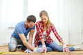 Smiling couple measuring wood flooring repair building and home concept Stock Photo