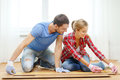 Smiling couple measuring wood flooring repair building and home concept Royalty Free Stock Image