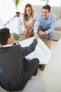 Smiling couple in meeting with a financial adviser high angle view of young at home Stock Photos