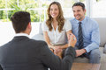 Smiling couple in meeting with a financial adviser young at home Royalty Free Stock Image