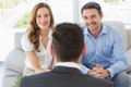 Smiling couple in meeting with a financial adviser young at home Royalty Free Stock Photo