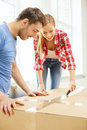Smiling couple opening big cardboard box repair building and home concept Stock Photo