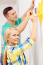 Smiling couple painting small heart on wall repair building and home concept at home Stock Photos