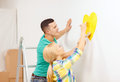 Smiling couple painting small heart on wall repair building and home concept at home Royalty Free Stock Images