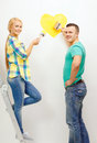 Smiling couple painting small heart on wall repair building and home concept at home Stock Photo