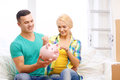 Smiling couple with piggybank in new home Royalty Free Stock Photo
