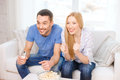 Smiling couple with popcorn cheering sports team Royalty Free Stock Photo