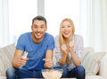 Smiling couple with popcorn cheering sports team food love family entretainment and happiness concept at home Royalty Free Stock Photography