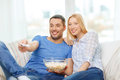 Smiling couple with popcorn watching movie at home food love family and happiness concept Royalty Free Stock Photography