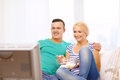 Smiling couple with popcorn watching movie at home food love family and happiness concept Stock Images