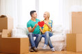 Smiling couple with red heart on sofa in new home moving and concept Royalty Free Stock Images