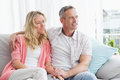 Smiling couple relaxing on the couch at home in living room Stock Image