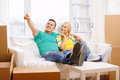 Smiling couple relaxing on sofa in new home moving and concept and pointing finger Royalty Free Stock Image