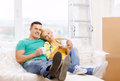 Smiling couple relaxing on sofa in new home moving and concept with tea cups Royalty Free Stock Photography