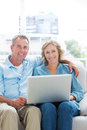 Smiling couple relaxing on their couch using the laptop looking at camera at home in sitting room Stock Photos