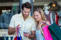 Smiling couple with shopping bags looking at smartphone