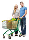 Smiling couple with shopping cart and food in it happiness concept Royalty Free Stock Photography