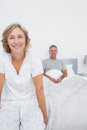 Smiling couple sitting on opposite ends of bed looking at camera in bedroom at home Stock Photo