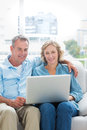 Smiling couple sitting on their couch using the laptop at home in room Stock Photo