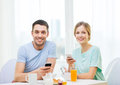 Smiling couple with smartphones reading news food home and technology concept and having breakfast at home Royalty Free Stock Image