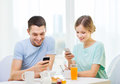 Smiling couple with smartphones reading news food home and technology concept and having breakfast at home Royalty Free Stock Photos