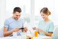Smiling couple with smartphones taking picture food home and technology concept teaking of breakfast at home Royalty Free Stock Images