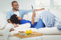 Smiling couple on the sofa reading newspaper together Royalty Free Stock Image