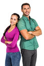 Smiling couple standing back to back with arms crossed looking at the camera on white screen Royalty Free Stock Images