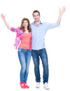 Smiling couple standing with raised hands full portrait of isolated on white background Stock Image
