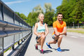 Smiling couple stretching leg outdoors Royalty Free Stock Photo