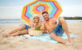Smiling couple sunbathing on the beach summer holidays vacation and happy people concept lying under colorful umbrella and showing Royalty Free Stock Photography