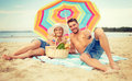 Smiling couple sunbathing on the beach summer holidays vacation and happy people concept lying under colorful umbrella and showing Royalty Free Stock Image