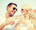 Smiling couple in sunglasses drinking wine in cafe Royalty Free Stock Photo