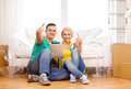 Smiling couple with tablet pc in new home moving technology and concept sitting on the floor computer showing thumbs up Royalty Free Stock Image