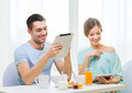 Smiling couple with tablet pc reading news food home and technology concept and having breakfast at home Stock Image