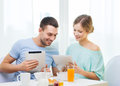 Smiling couple with tablet pc reading news food home and technology concept and having breakfast at home Royalty Free Stock Image