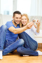 Smiling couple taking picture with digital camera love family technology and happiness concept self portrait at home Royalty Free Stock Photography
