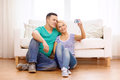 Smiling couple taking picture with digital camera love family technology and happiness concept self portrait at home Stock Photos