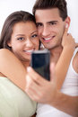 Smiling couple taking a picture with mobile phone portrait of cheerful young Stock Image