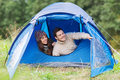 Smiling couple of tourists looking out from tent Royalty Free Stock Photo
