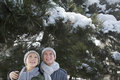 Smiling couple under tree covered in snow Royalty Free Stock Image