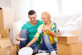 Smiling couple unpaking boxes with kitchenware moving home and concept in new home Stock Photo