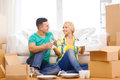 Smiling couple unpaking boxes with kitchenware moving home and concept in new home Royalty Free Stock Image