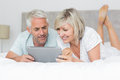 Smiling couple using digital tablet in bed mature at home Royalty Free Stock Image