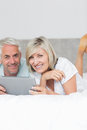 Smiling couple using digital tablet in bed mature at home Stock Photo